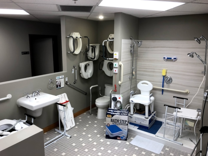A photo of the bathroom accessories and home modifications at Oswald's Pharmacy. A mock shower, toilet, and sink can be seen displaying home bathroom mods for handicap accessibility.
