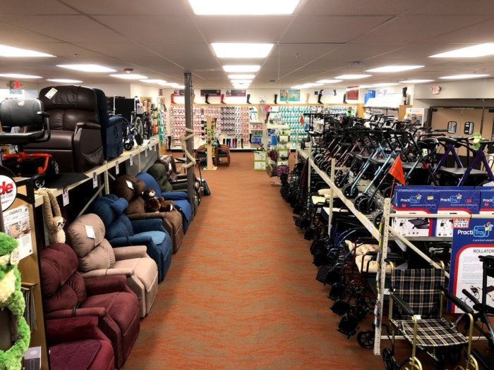 A photo of the Oswald's Pharmacy Medical Equipment Showroom floor. The image looks down an aisle with 10 lift chairs and a few mobility scooters on the left and wheelchairs & rollators on the right.