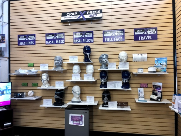 A photo of the CPAP mask display at Medical Xpress. 12 masks are displayed on mannequin busts with CPAP units and accessories displayed on both sides.