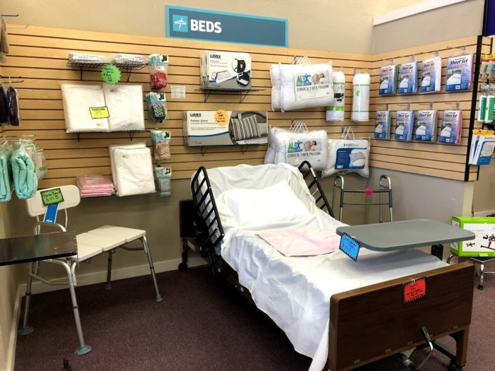 A photo of a hospital bed display. A home medical hospital bed is shown with rails, an overbed table, and various other accessories surrounding it.