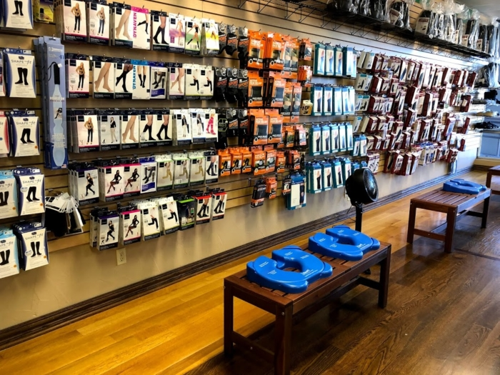 Photo of a wall display of compression hosiery, compression sleeves, and braces & supports. A shelf on top of the display holds CAM walking boots.