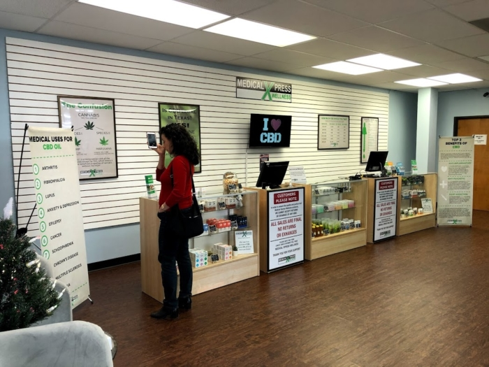 A photo of the CBD counter at Medical Xpress. A woman is browsing the CBD and hemp products displayed in glass showcases.